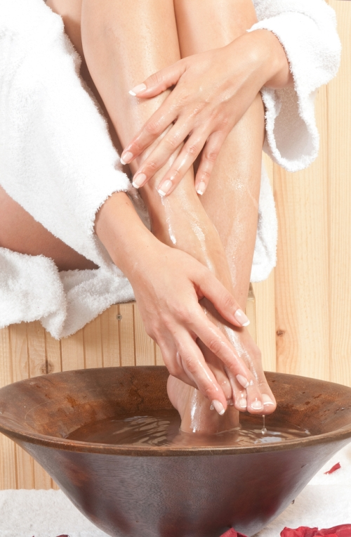 ladies feet soaking in a foot bath