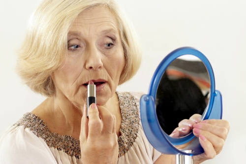 Mature woman holding a mirror and applying lipstick