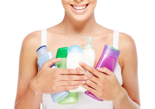 Young woman holding bottles of moisturizers