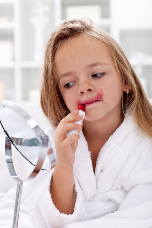 Little girl putting pink lipstick all over her face.