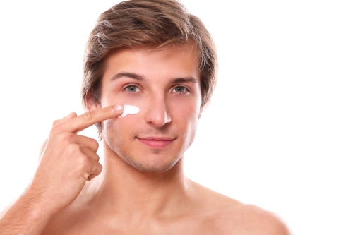 Young man applying moisturizer