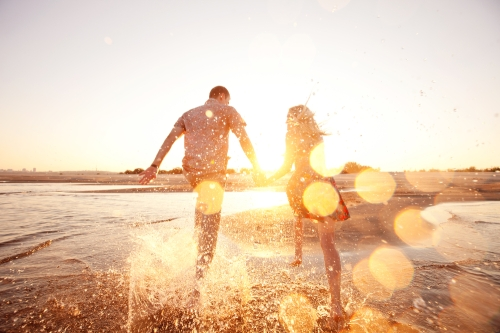 couple playing in the water at the beach