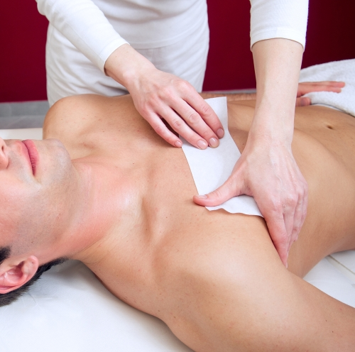 Young man getting his chest waxed