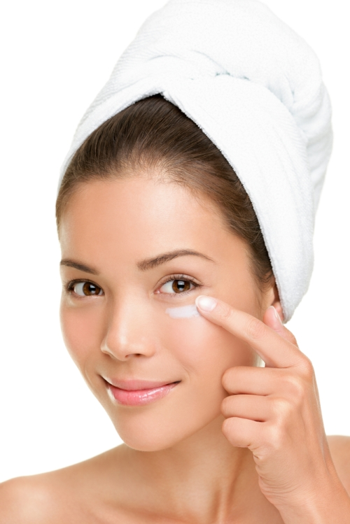 Young lady applying eye cream