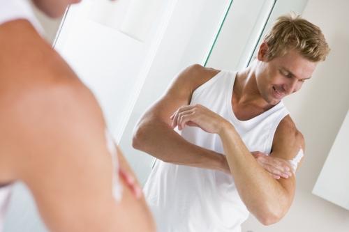 Man applying body moisturizer