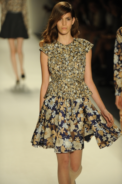 Model in mixed prints going down the runway