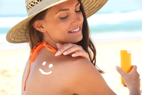 Woman applying sun block at the beach with wide brimmed hat on