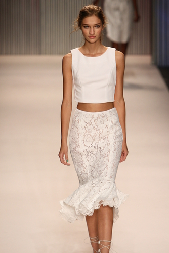 Model wearing all white outfit down runway