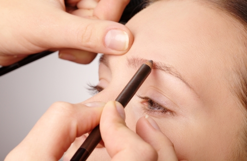 Makeup artist penciling eyebrow makeup