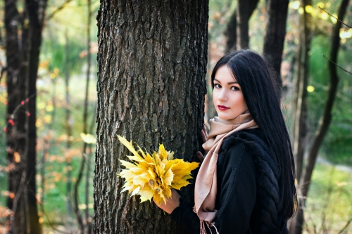 Young woman with autumn leaves and dark hair color