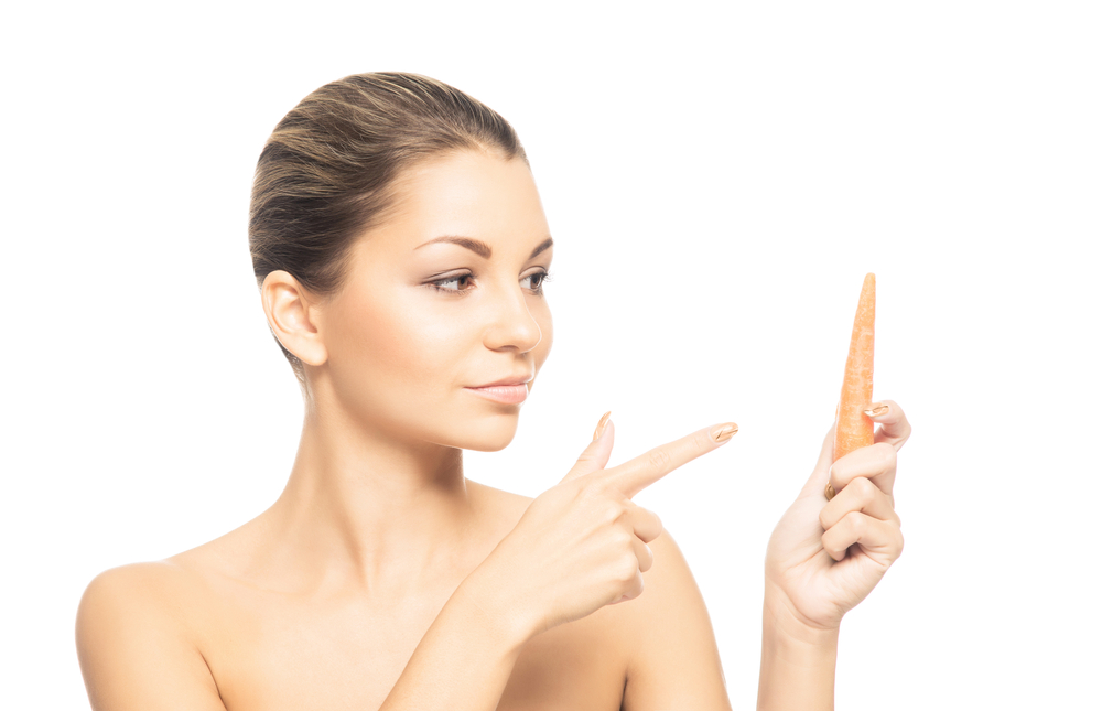 Young woman with beautiful skin pointing to a carrot
