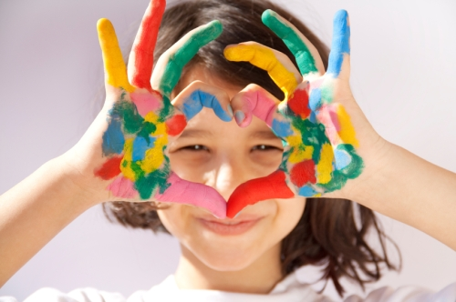 Young girl with various color paints smeared on her hands making a heart shape with her fingers