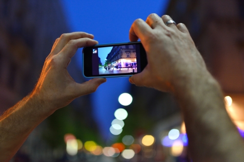 Using a smart to take photos during the evening on a light up street