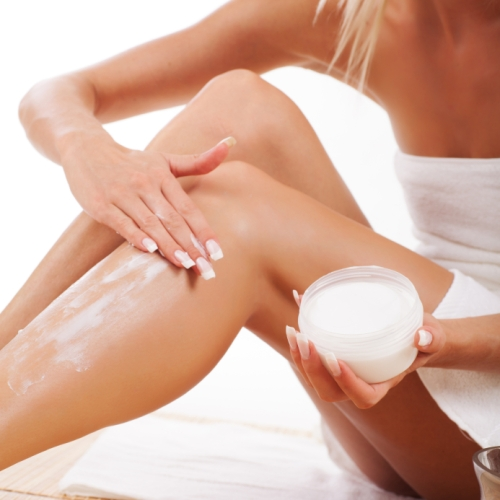 Woman applying moisturizer to her legs form a big tub of lotion