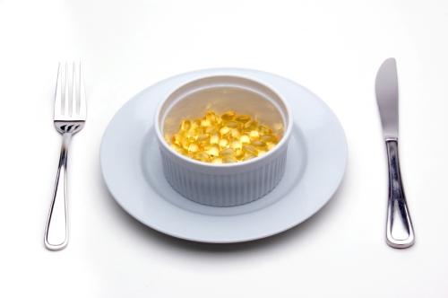 Vitamin E Caplets In A White Ramekin Dish, Set For Lunch