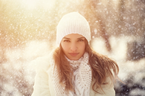 Young woman outdoors in the snowy winter contemplates skincare