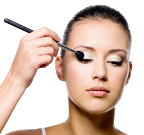 beautiful young woman applying eyeshadow with brush on white background