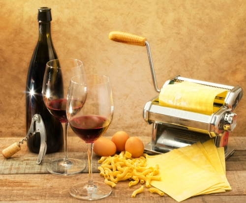 Bottle of Chianti with some poured in glasses standing near food pairings like pasta