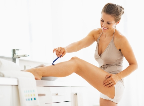 Woman shaving her legs in the bathroom.
