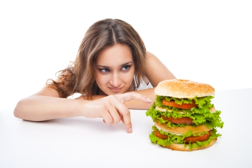 Young woman eating a huge burger