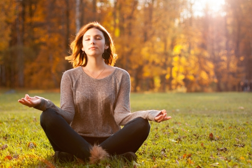 Woman meditating in a park.
