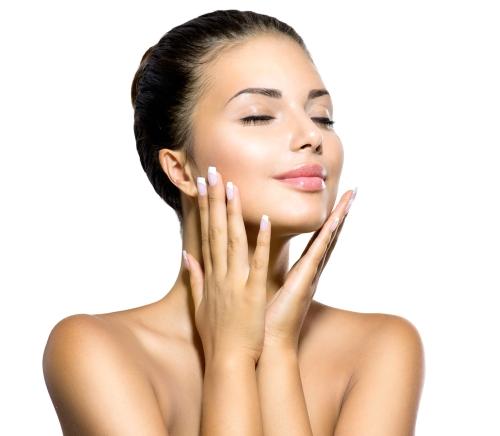 Woman feeling her freshly cleansed face.