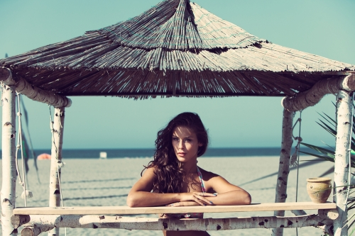 Attractive woman enjoying herself under the shade in a beach.