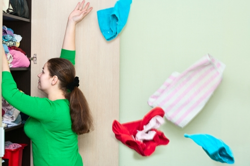 Caucasian woman getting rid of last year's clothes.