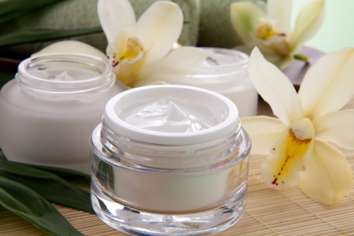 A jar of moisturizer cream in front of beautiful white orchid flowers.