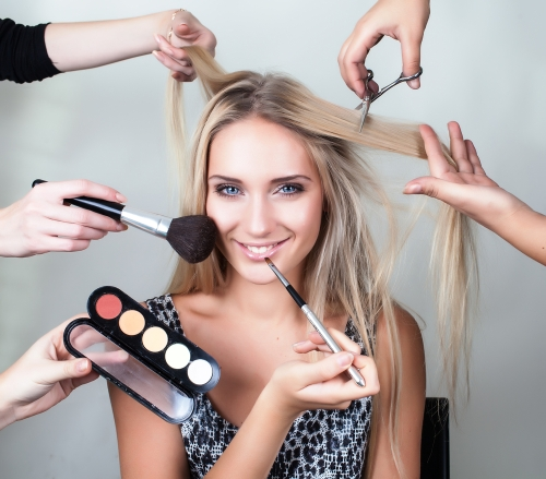 Many hands helping a woman apply her makeup and complete her beauty routine.