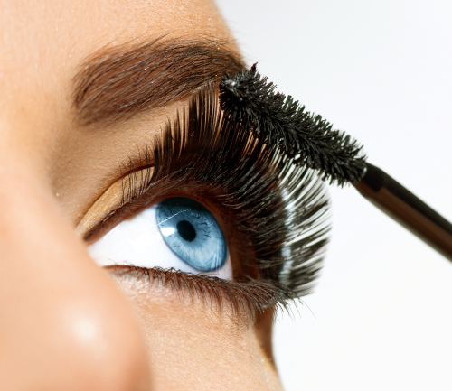Woman applying mascara on her beautiful eyelashes.