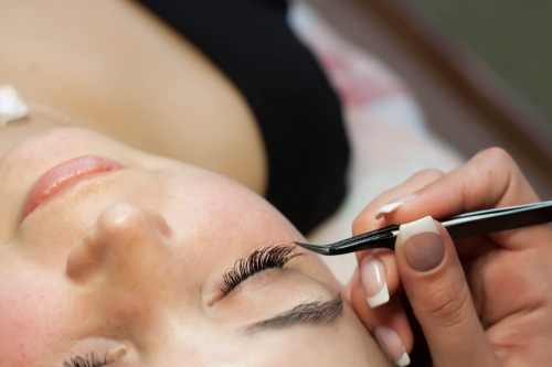 Woman getting eyelash extensions applied in a salon.
