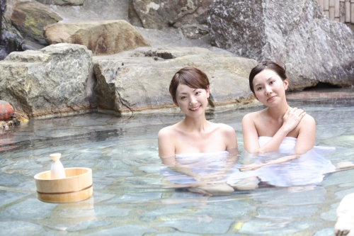 Japanese woman bathing in a hot spring and drinking sake.