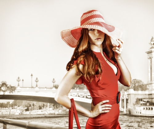 Woman in a red colored dress and red belt with a white and red hat.