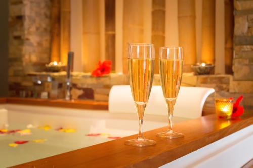 Two glasses of champagne on a bath tub.
