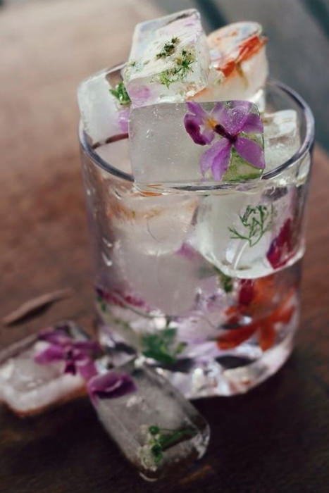 Edible flowers frozen inside ice cubes being served at a party.