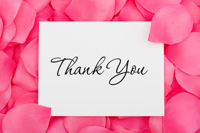 Thank You written on a white paper with a pink background.