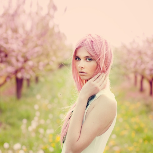 Woman with pink hair in a park.
