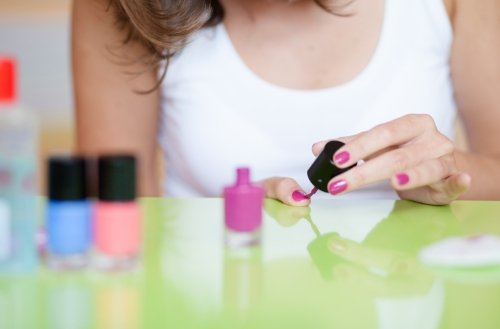Closeup of a woman applying nail polish.
