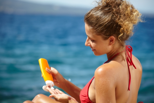 Woman applying sunscreen lotion.