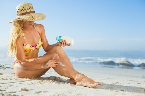 Woman applying sunscreen in a beach.