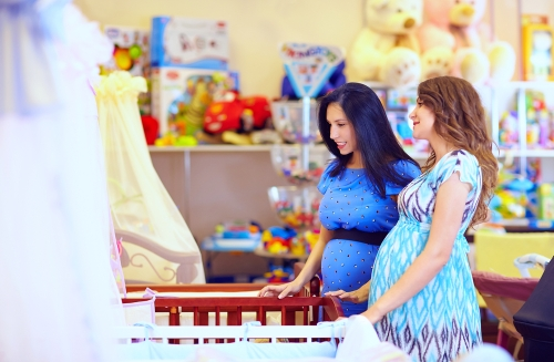 Mothers in maternity clothes choosing cots.
