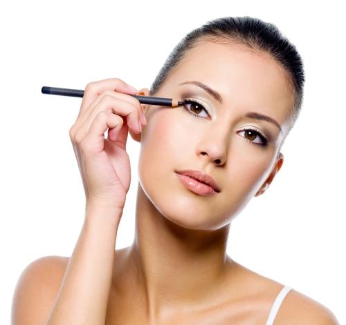 Woman applying a black eyeliner.