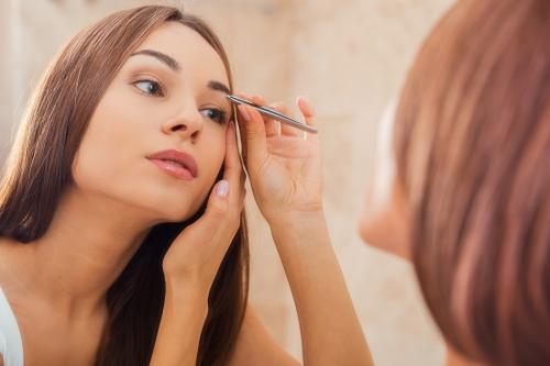 Woman tweezing her eyebrows.