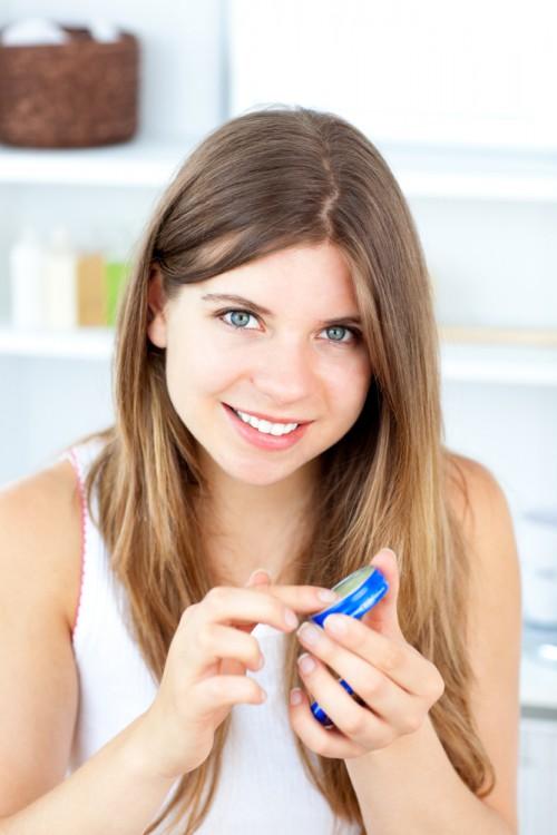 Woman applying vaseline on her lips.