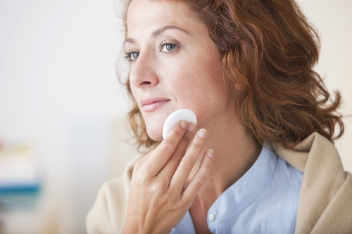 Mature woman removing makeup from her skin.