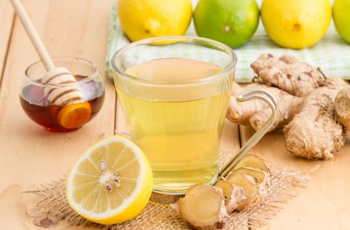 Cup of lemon tea surrounded by ingredients rich in vitamin C