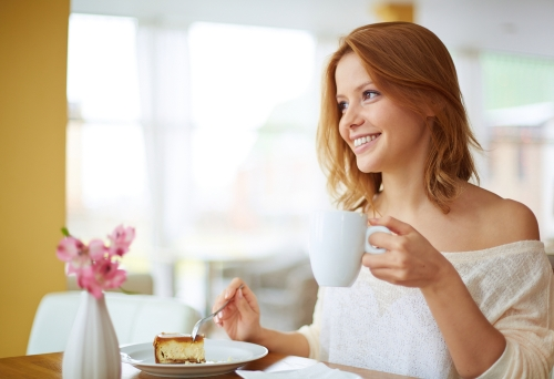 Woman having coffee and desserts in a cafe.