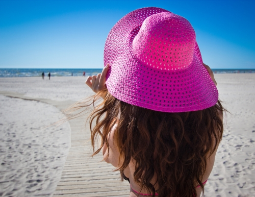 Woman wearing a large pink hat in a beach.