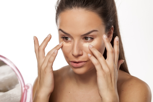 Woman applying an eye cream.
